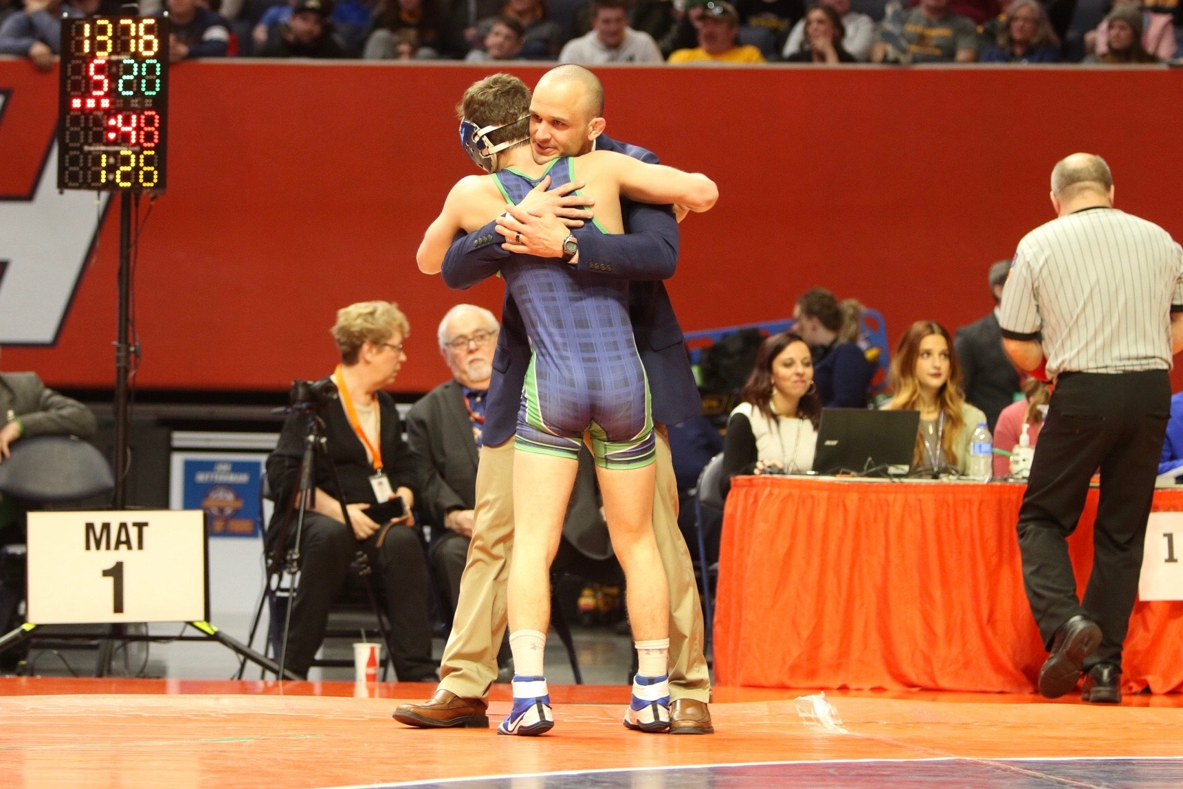 Tristan Daugherty hugs PND Assistant Coach Danny Burk after becoming the school's first state champion